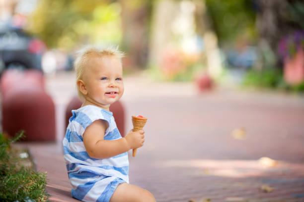 Niño bebé dulce, comer helado en un caluroso día de verano en el Parque - foto de stock