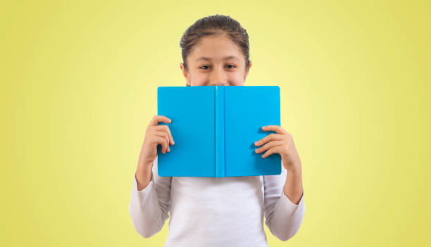 little sweet girl holding a book and looking at camera stock photo