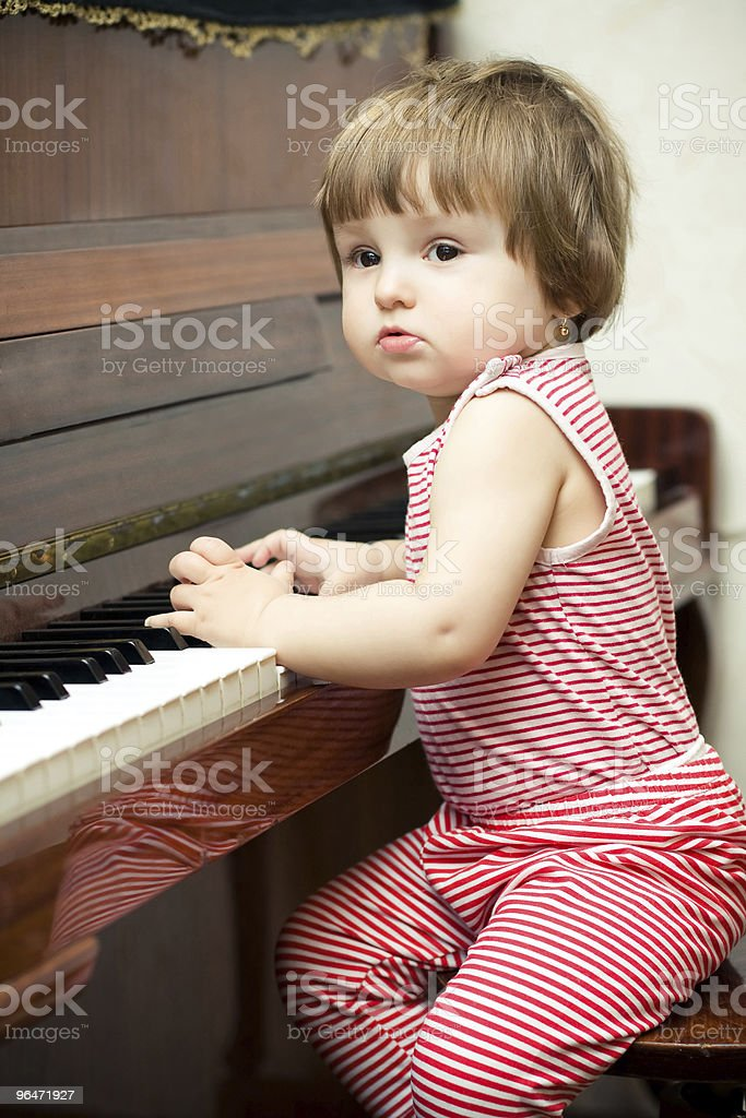 Little sweet girl plays piano royalty-free stock photo