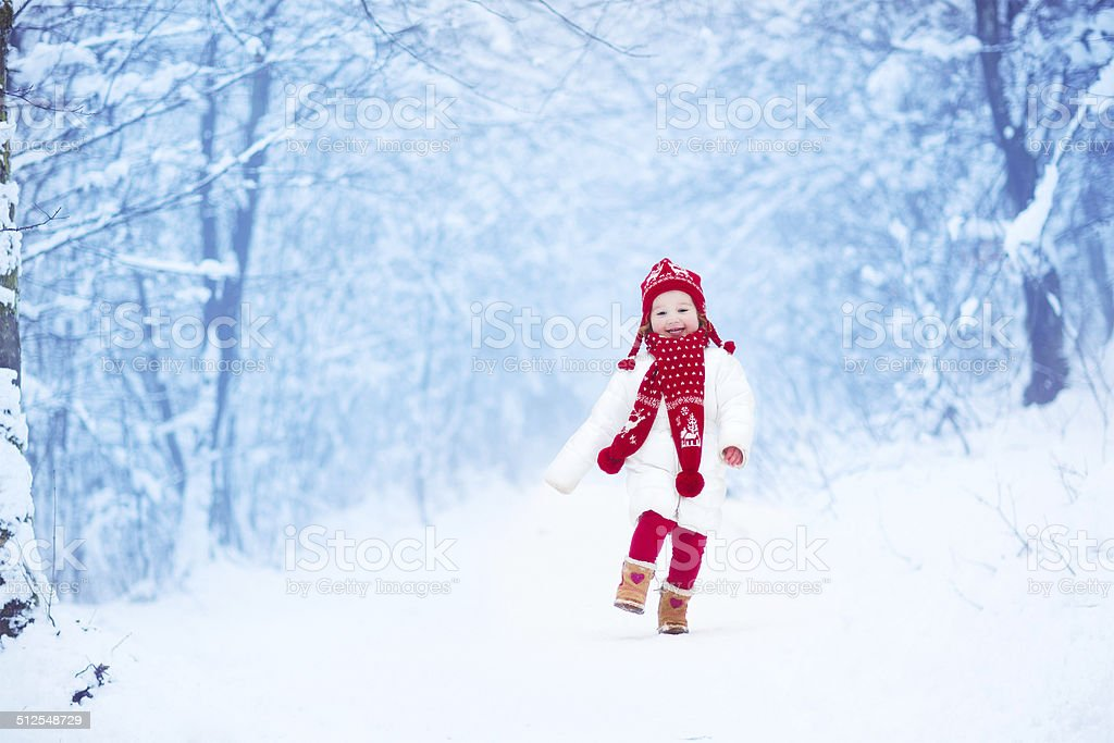 Little sweet girl running in a snowy park stock photo