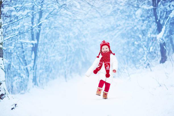 bisschen süßes mädchen laufen in einer verschneiten park - kinder winterstiefel stock-fotos und bilder
