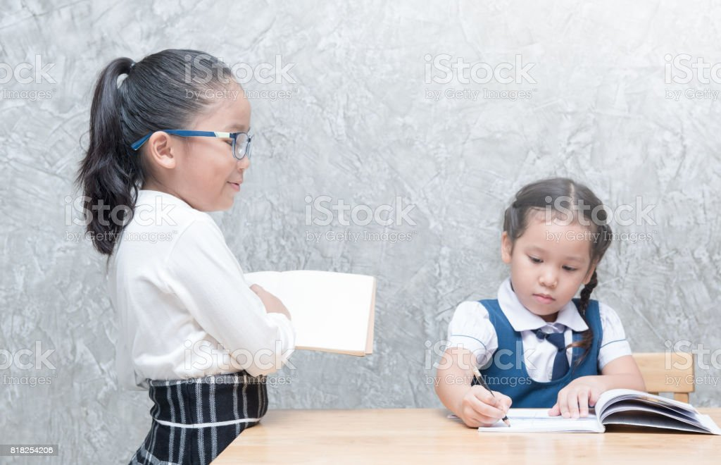 little teacher looking student to doing homework stock photo
