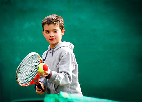 istock Little tennis player on a blurred green background 877754132
