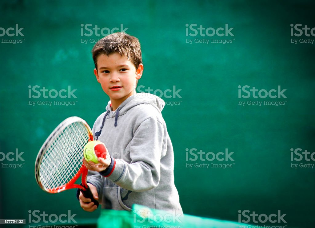 Little tennis player on a blurred green background stock photo