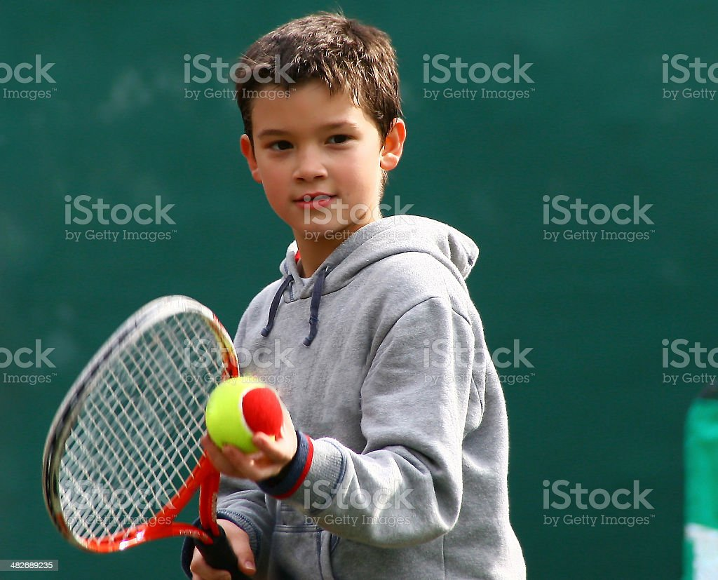 Little tennis player on a blurred green backround stock photo