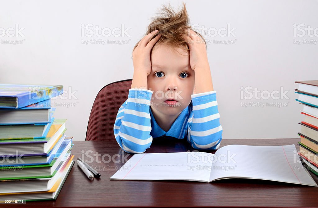 little tired boy sitting at the desk stock photo