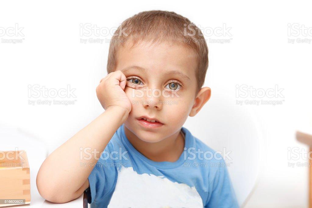 Poco cansado niño sentado en el escritorio - foto de stock