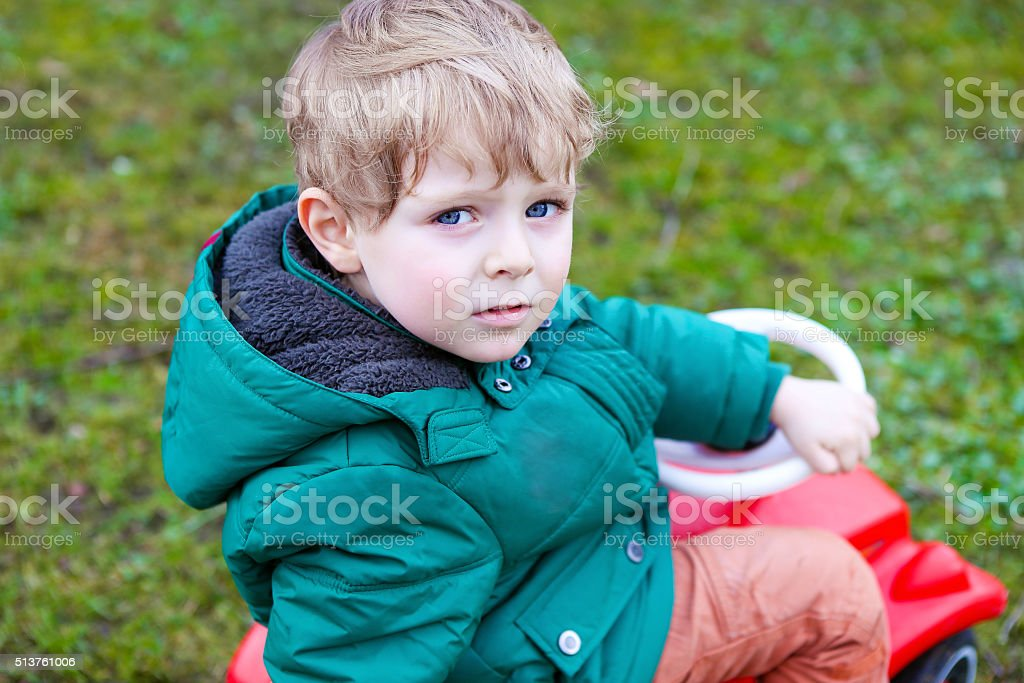 Little todder boy playing with big toy car stock photo