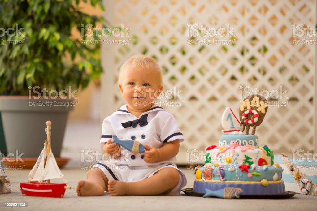 Little Toddler Boy Dressed As Sailor Celebrating His First Birthday With Sea Theme Cake
