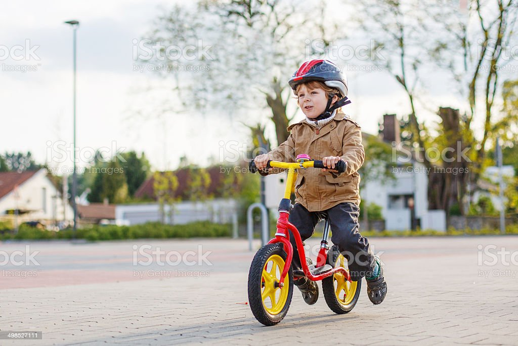 Little toddler boy having fun and riding his bike stock photo