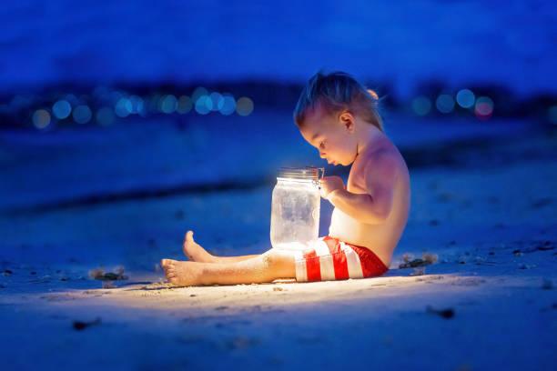 Niño pequeño, sentado en la playa después de la puesta del sol a la luz de la luna con una linterna, disfrutando de la quiteza de la playa - foto de stock