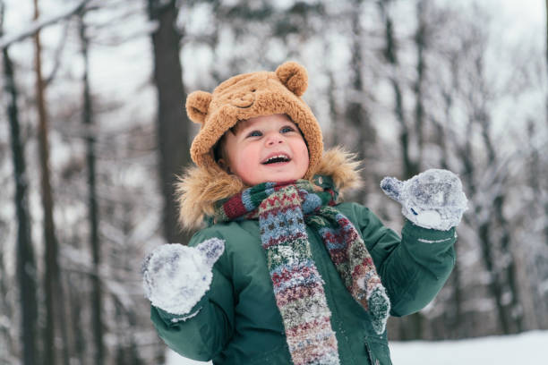 Little toddler boy walking in the winter forest and having fun with snow enjoying winter outdoors. Winter and lifestyle concept