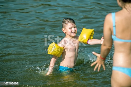istock little toddler boy with inflatable armbands aids playing in water with mother in lake water 1167406466