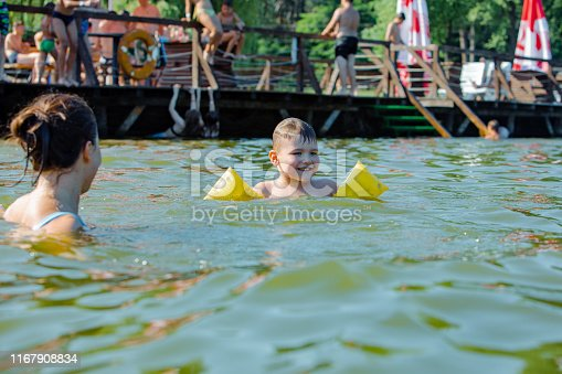 istock little toddler boy with inflatable armbands aids playing in water with mother in lake water 1167908834