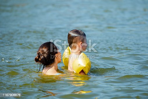 istock little toddler boy with inflatable armbands aids playing in water with mother in lake water 1167908876