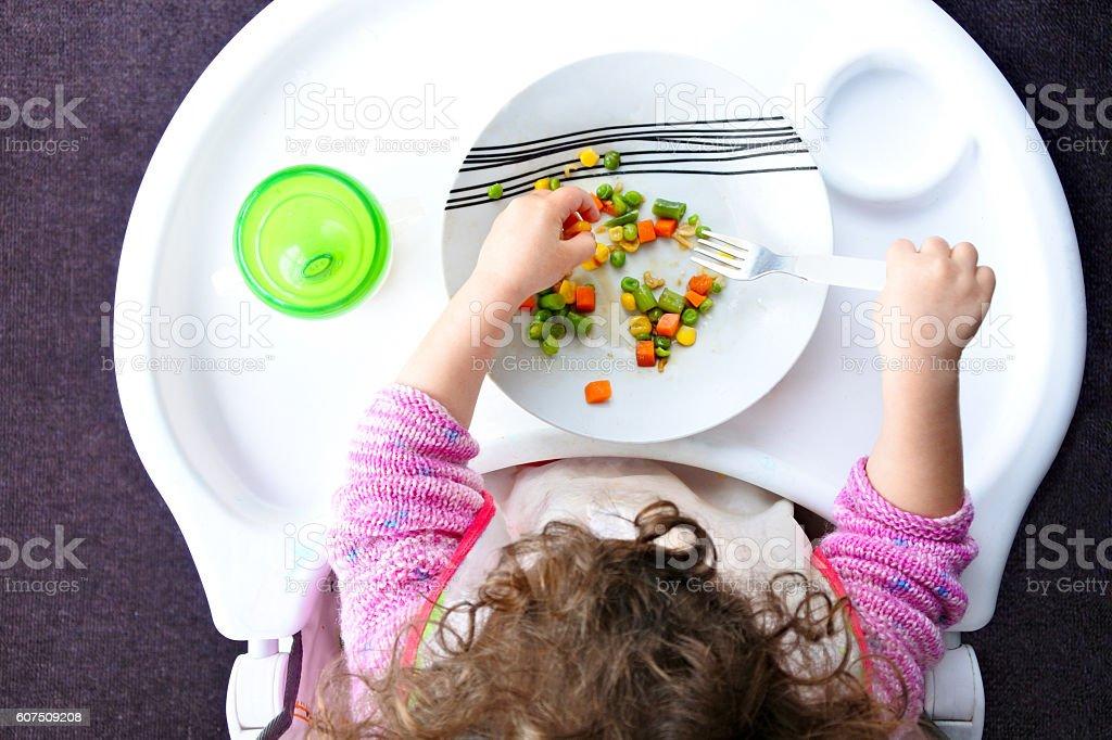 Little toddler child eats vegetables stock photo