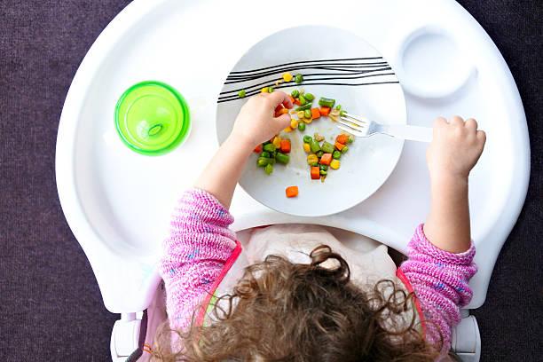 little toddler child eats vegetables - kinderstuhl und tisch stock-fotos und bilder
