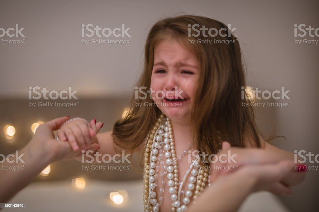 Little toddler girl crying at home stock photo