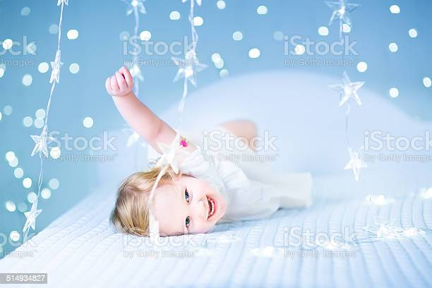 Little toddler girl in white bed between sparkling blue lights picture id514934827?b=1&k=6&m=514934827&s=612x612&h=9kunii1cf3z7mynxlxs3tvyb5xys79mjmqyg05i55ok=