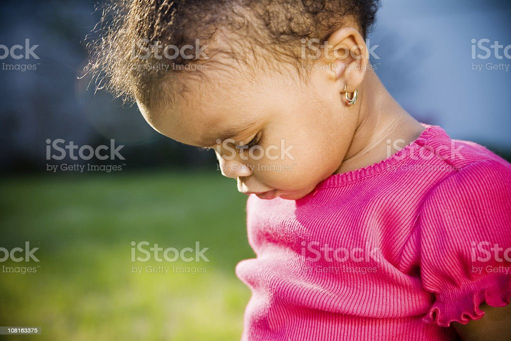 Little Toddler Girl Looking Down and Standing Outside stock photo