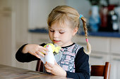 little toddler girl making craft apple with paper, colorful pompoms and glue during pandemic coronavirus quarantine disease. Happy creative child, homeschooling and home daycare with parent.