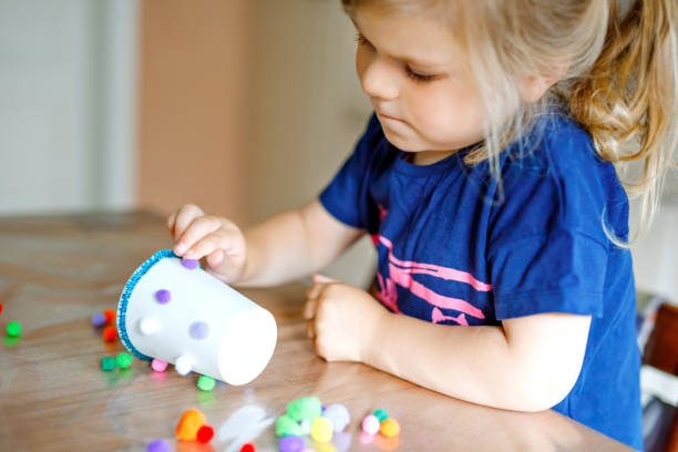 little toddler girl making craft lantern with paper cups, colorful pompoms and glue during pandemic coronavirus quarantine disease. Happy creative child, homeschooling and home daycare with parents stock photo