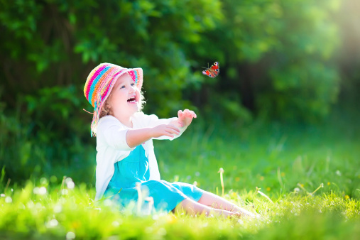 Little toddler girl playing with butterfly