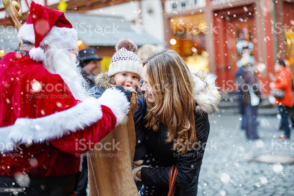 Kleines Mädchen mit Mutter auf dem Weihnachtsmarkt. Lizenzfreies stock-foto