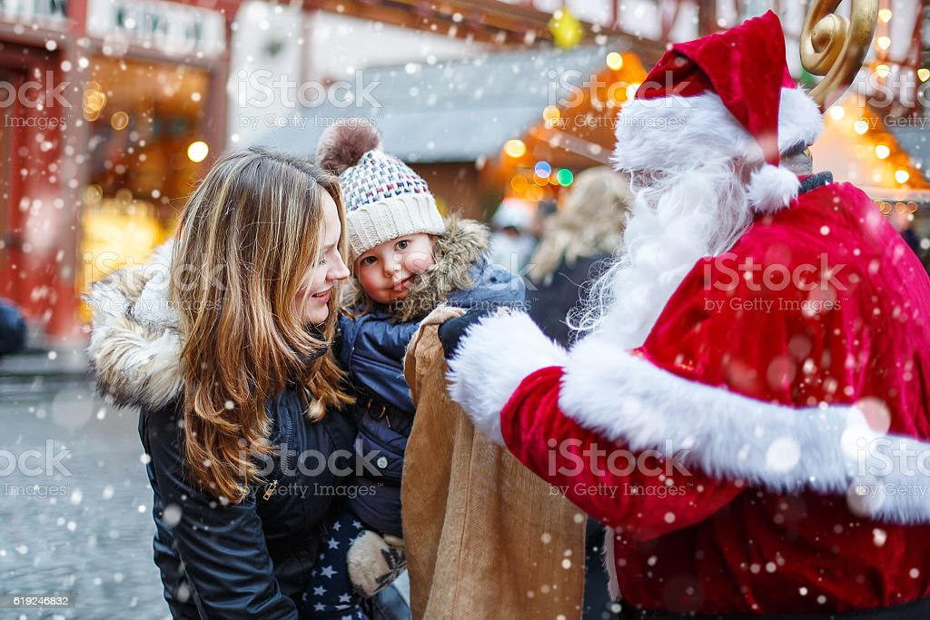 Kleines Mädchen mit Mutter auf dem Weihnachtsmarkt. – Foto