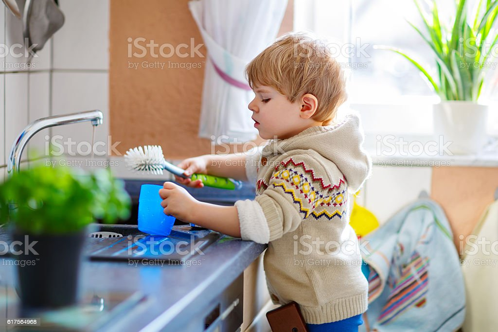 Little toddler helping in kitchen with washing dishes stock photo