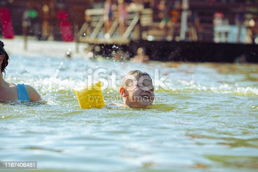 istock little toddler kid swimming in lake with inflatable arms aids support 1167406451