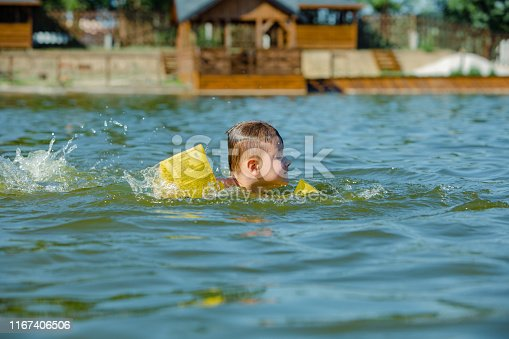 istock little toddler kid swimming in lake with inflatable arms aids support 1167406506