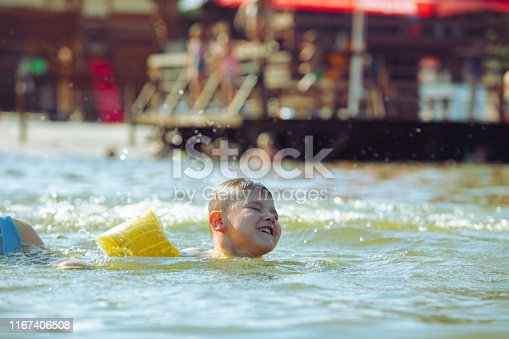 istock little toddler kid swimming in lake with inflatable arms aids support 1167406508