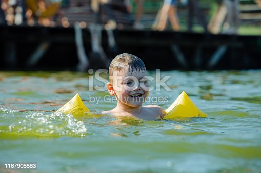 istock little toddler kid swimming in lake with inflatable arms aids support 1167908883