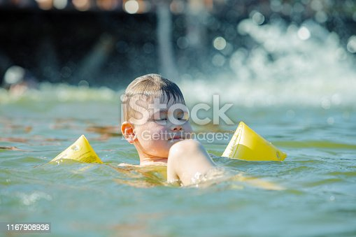 istock little toddler kid swimming in lake with inflatable arms aids support 1167908936