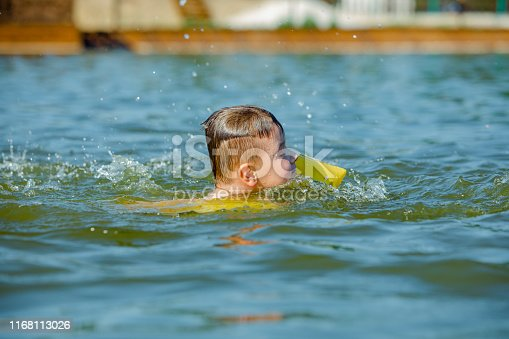 istock little toddler kid swimming in lake with inflatable arms aids support 1168113026