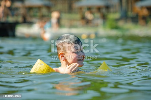 istock little toddler kid swimming in lake with inflatable arms aids support 1168880304