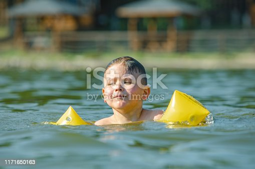 istock little toddler kid swimming in lake with inflatable arms aids support 1171650163