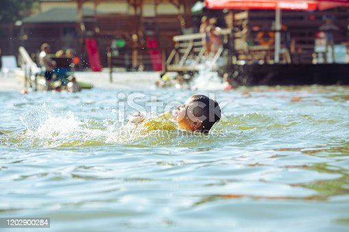 istock little toddler kid swimming in lake with inflatable arms aids support 1202900284