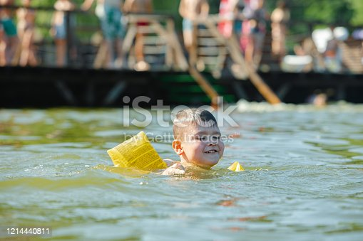 istock little toddler kid swimming in lake with inflatable arms aids support 1214440811
