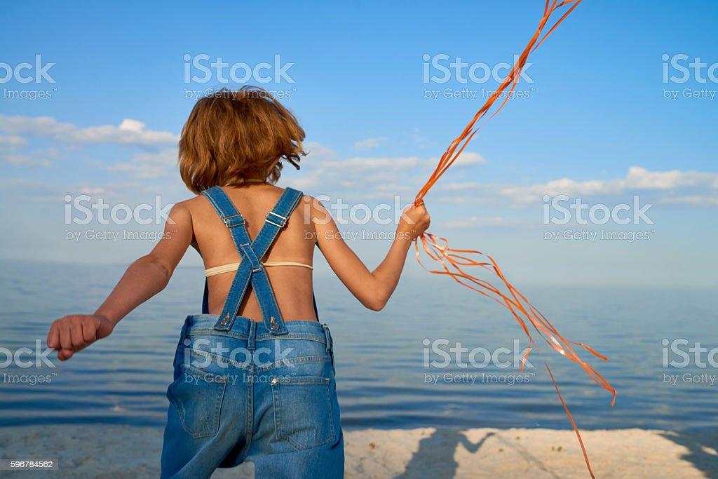 Little Tomboy Girl Running at Beach stock photo