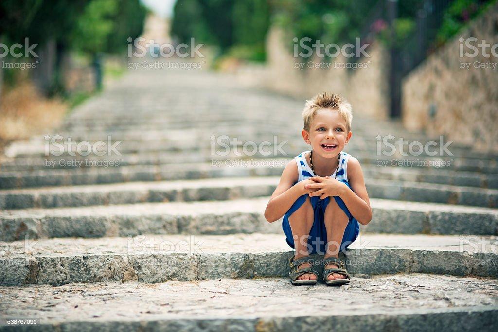 Little tourist boy sitting on Pollensa stairs stock photo