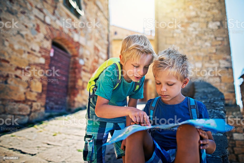 Little tourist boys checking map in a small Italian town stock photo