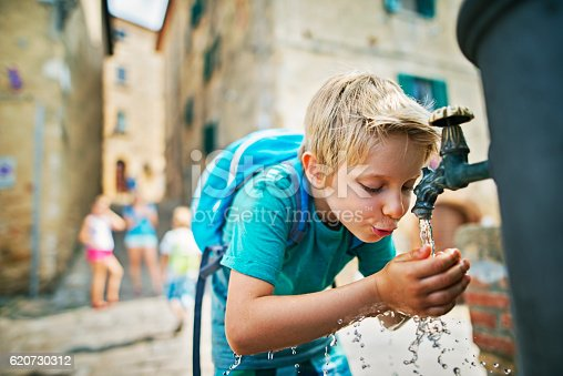 Family is visiting beautiful italian town. The boy is splashing his face and drinking from the public fountain. Mother and other kids are visible in the background.