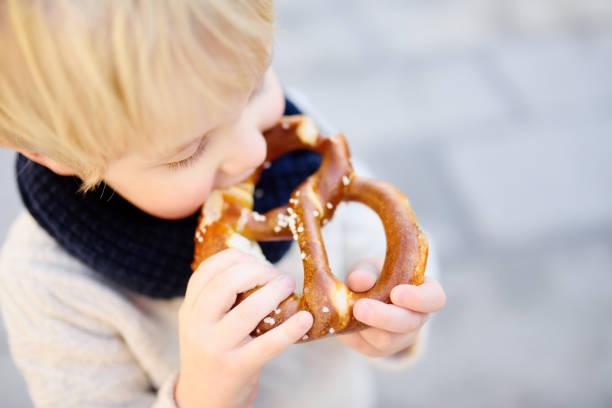 小遊客持有傳統的巴伐利亞麵包叫椒鹽脆餅在市政廳建築背景在慕尼克, 德國 - 椒鹽蝴蝶圈 個照片及圖片檔