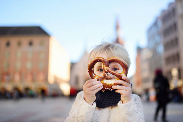 Little tourist holding traditional bavarian bread called pretzel on the town hall building background in Munich, Germany stock photo