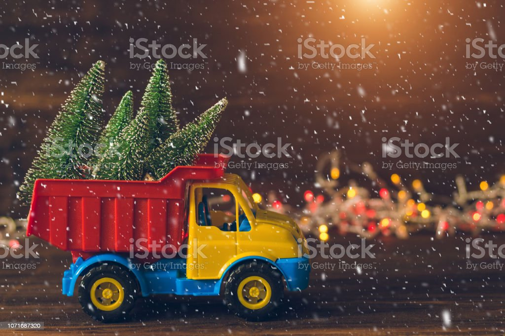Little Toy Truck Carrying Christmas Trees During Snowfall