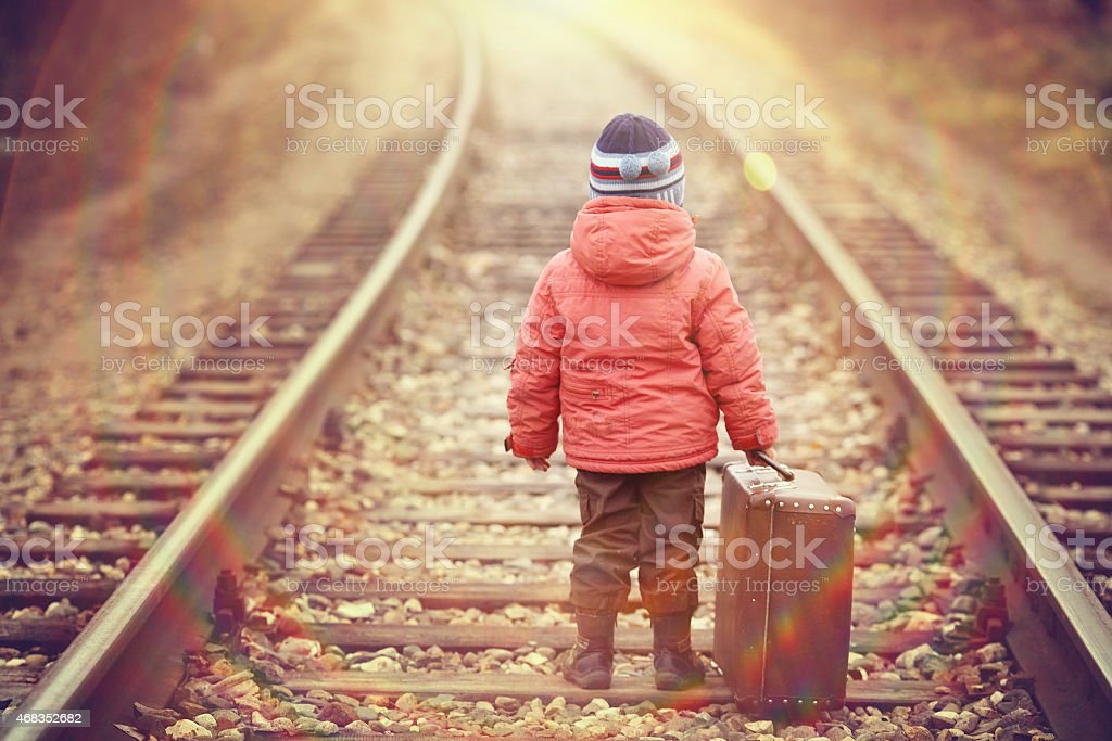 little traveler with a suitcase on the railroad royalty-free stock photo