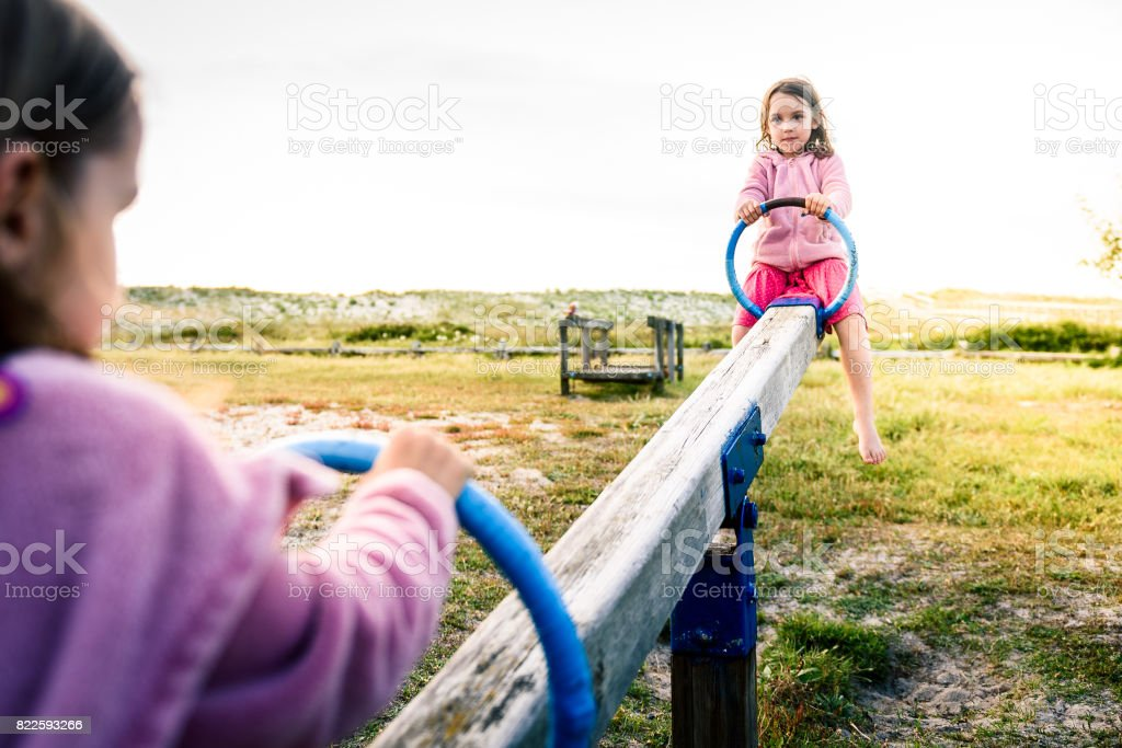 Little twin girls children are riding seesaw swing in park. stock photo