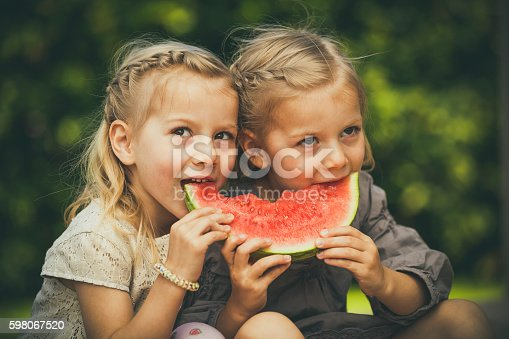 sweet little twin girls eating melon in the garden.